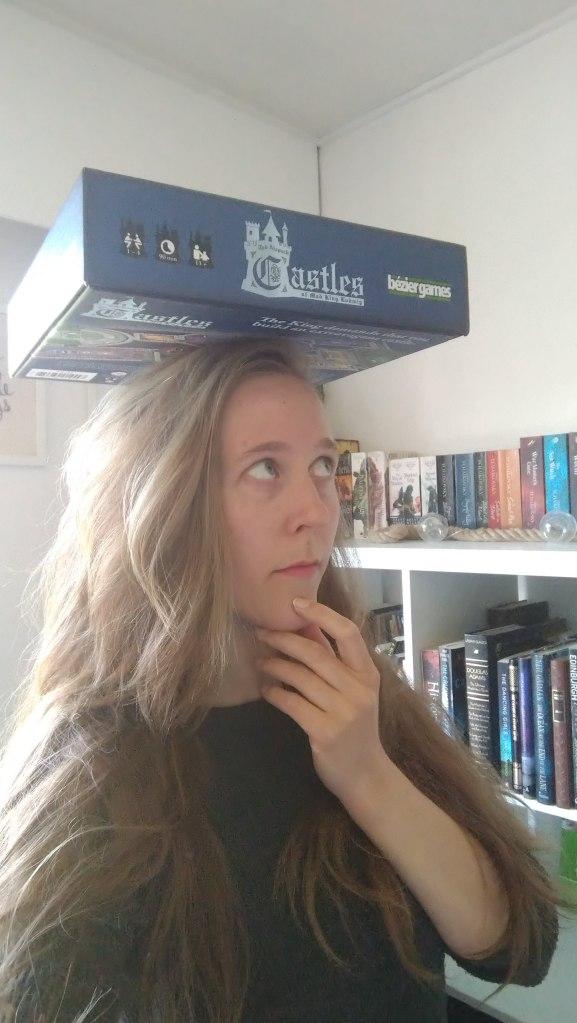 Woman balancing boardgame on top of head